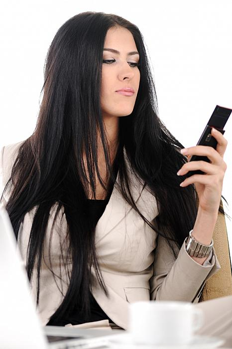 kozzi-24944852-view of beautiful business woman holding cell phone and speaking on-588x884