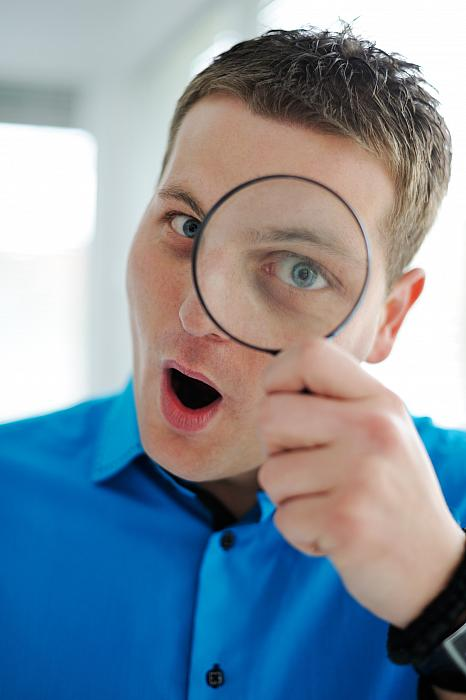 kozzi-2092547-portrait of a young business man with magnifying glass-1590x2389