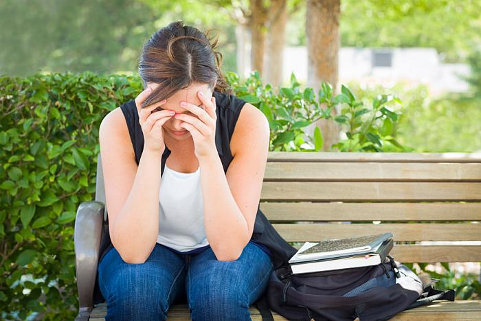 kozzi-5668423-upset young woman sitting alone on bench next to books-883x588