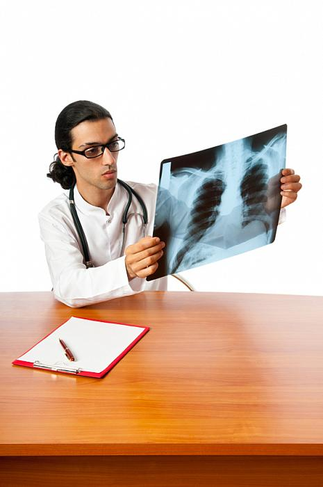kozzi-Male doctor looking at x-ray image-587x884