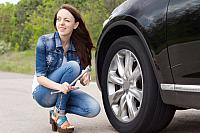 kozzi-10447876-Smiling young woman getting ready to change a tyre-883x588