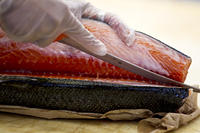 kozzi-close-up of chef cutting a fresh filet of salmon-1774x1183